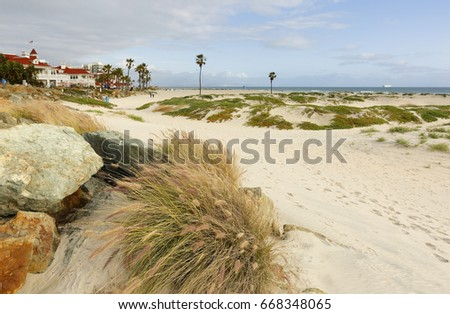 Coronado beach at sunset. Photo shows a sand dune and dry grass in foreground and Hotel del Coronado in the background.