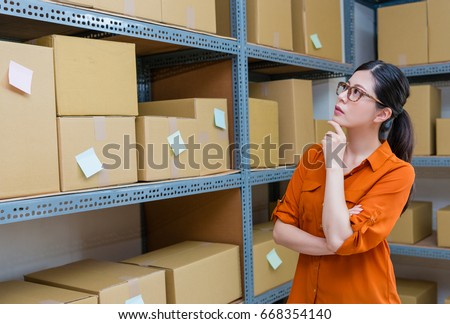 beautiful young female online shopping owner looking at warehouse stock box and thinking shipping order how to processing.