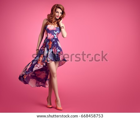 Fashion Sensual Sexy Redhead Model Smiling. Beauty Woman in Summer Outfit. Trendy Floral Dress, Stylish Curly Wavy hairstyle, Luxury Heels. Playful Romantic Lady on Pink.  #668458753