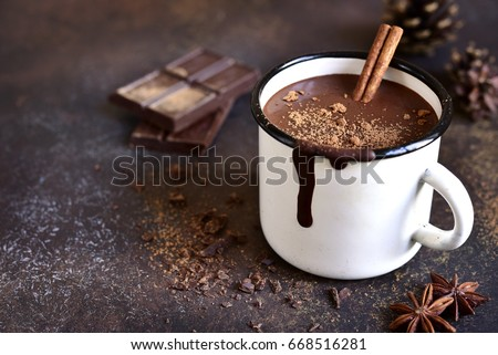 Homemade spicy hot chocolate with cinnamon in enamel mug on a slate,stone or concrete background. Royalty-Free Stock Photo #668516281