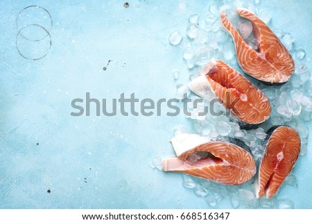 Steaks of raw salmon on ice on a blue slate,stone or metal background.Top view with space for text. Royalty-Free Stock Photo #668516347