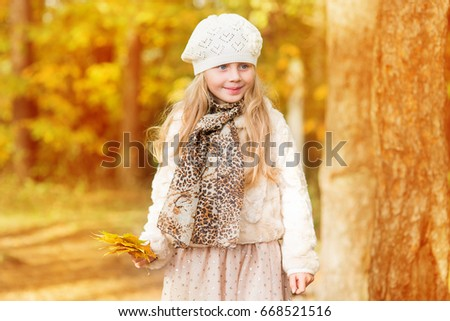 little girl in warm cardigan smiling against the background of fallen leaves #668521516