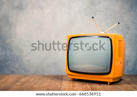 Retro old orange TV receiver on table front textured concrete wall background. Vintage style filtered photo
