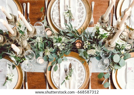 Aerial view of winter green garland on a wedding receptions head table with gold place setting and candelabra Royalty-Free Stock Photo #668587312