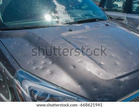 Dented car after a big hail storm Royalty-Free Stock Photo #668621941