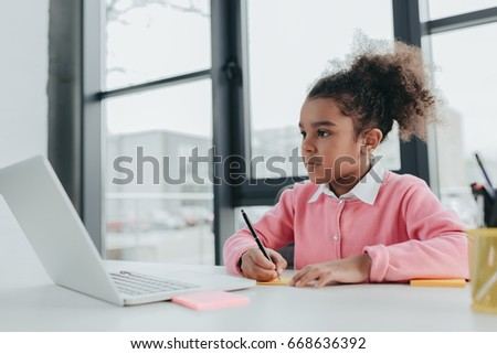Adorable little african american girl using laptop while sitting at office table #668636392