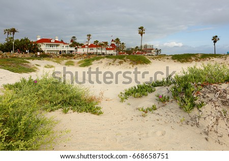 Coronado beach at sunset. Photo shows sand dune with green grass in foreground and Hotel del Coronado in the background.
