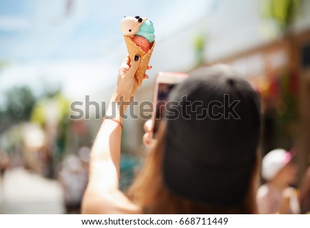 Pretty girl taking picture of ice cream on smartphone. Focus on ice cream
