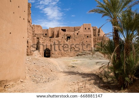 Entrance arch in the wall of an ancient Moroccan fortress. Tamnougalt, Morocco. #668881147