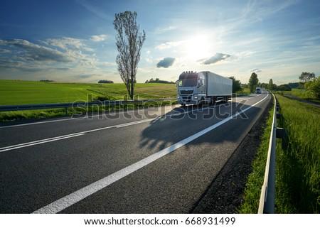 White trucks driving on asphalt road along the green fields in rural landscape at sunset #668931499