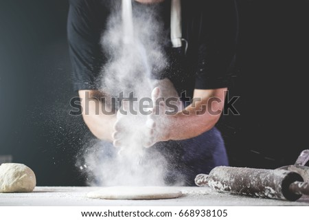 close-up of human hands in the apron knead the dough on a black wooden table, sprinkle with flour.Making dough by hands at bakery. #668938105