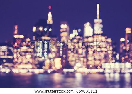 Blurred vintage toned Manhattan waterfront skyline at night, New York City, USA.