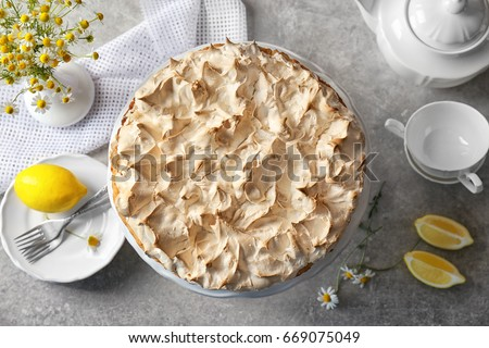 Composition with tasty lemon meringue pie on kitchen table