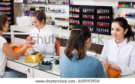 Young women getting manicure by professional manicurist in beauty salon #669093904