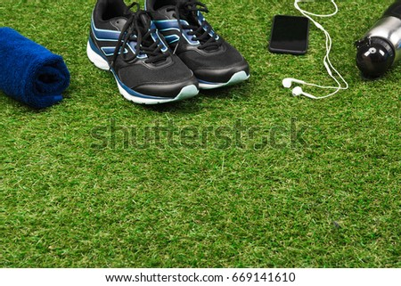 trainers, smartphone, towel and sport bottle on grass field #669141610