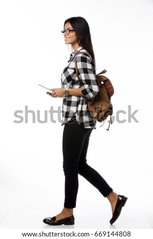 Full length portrait of smiling female student wearing glasses and  plaid shirt with tablet computer and backpack walking side. over white background #669144808