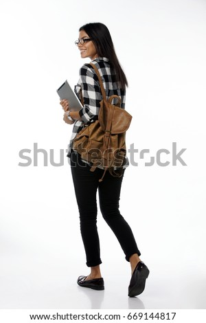 Full length portrait of young female student in glasses and  plaid holding tablet computer and backpack walking away from camera. isolated on white background #669144817
