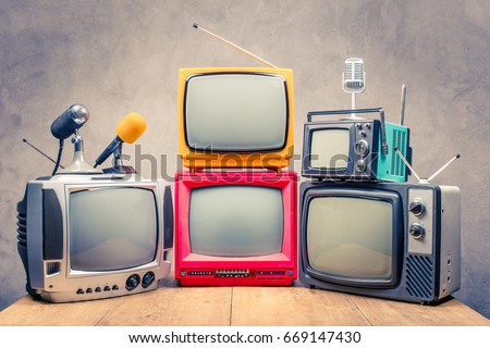 Retro old TV set receivers and microphones on table front textured concrete wall background. Broadcasting concept. Vintage style filtered photo Royalty-Free Stock Photo #669147430