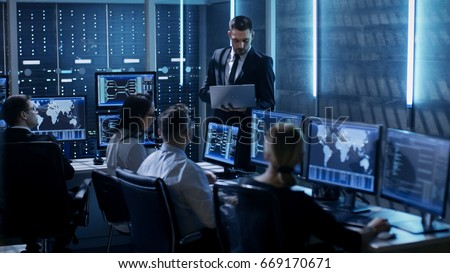 Professional IT Engineers Working in System Control Center Full of Monitors and Servers. Supervisor Holds Laptop and Holds a Briefing. Possibly Government Agency Conducts Investigation.  #669170671