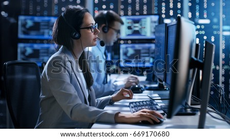 Female working in a Technical Support Team Gives Instructions with the Help of the Headsets. In the Background People Working and Monitors Show Various Information.  Royalty-Free Stock Photo #669170680