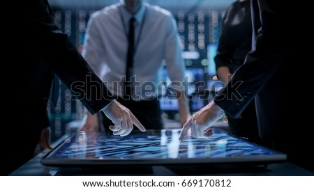 Corporate Managers Working at the Table in Monitoring Room. Room is Full of State of the Art Technology. Computers with Animated Screens. Royalty-Free Stock Photo #669170812