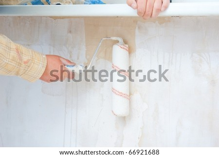 hand in roller painting wall #66921688