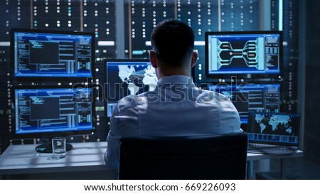 System Security Specialist Working at System Control Center. Room is Full of Screens Displaying Various Information. Royalty-Free Stock Photo #669226093