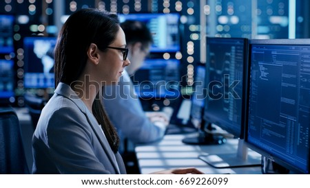 Female Engineer Controller Observes Working of the System. In the Background People Working and Monitors Show Various Information. #669226099