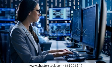 Female Engineer Controller Observes Working of the System. In the Background People Working and Monitors Show Various Information. #669226147