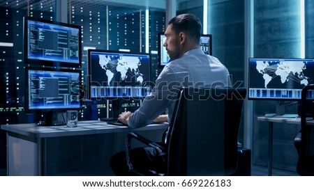 Technical Controller Working at His Workstation with Multiple Displays. Displays Show Various Technical Information. He's Alone in System Control Center. #669226183