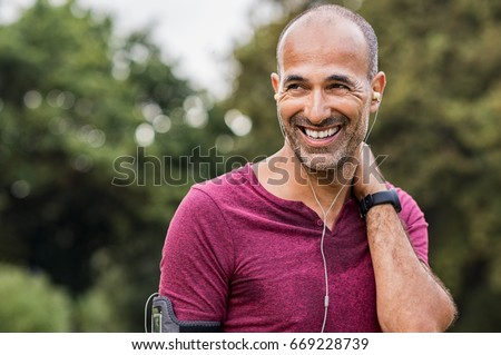 Mature man listening to music while resting after jogging. Happy senior man feeling refreshed after exercise. Portrait of a multiethnic man looking away in park while listening to music after fitness. #669228739