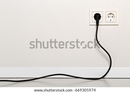 Black power cord cable plugged into european wall outlet on white plaster wall with copy space Royalty-Free Stock Photo #669305974