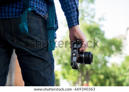 Photographer standing and holding camera  #669340363