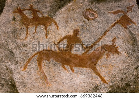 Drawing of an ancient man in a cave depicting a rider. A rider with a flag in his hand. Petrographic. history. archeology.