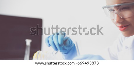 Woman researcher is surrounded by medical vials and flasks, isolated on white background #669493873