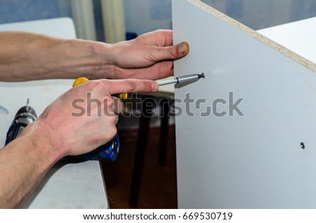 Worker assemble chipboard furniture with the screwdriver #669530719