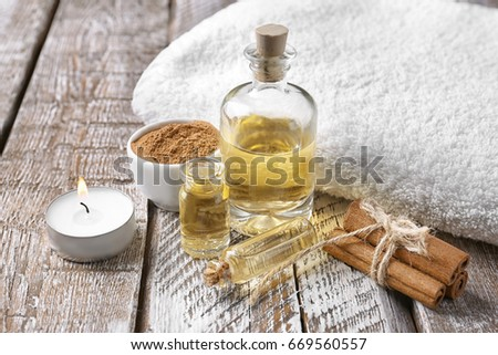Composition with bottles of cinnamon oil on wooden background #669560557
