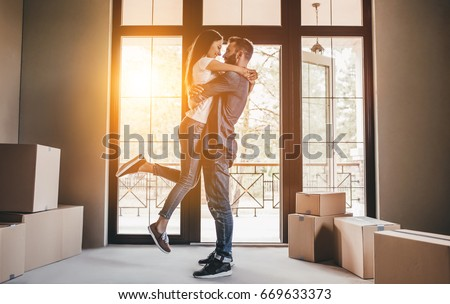Happy couple with cardboard boxes in new house at moving day. #669633373