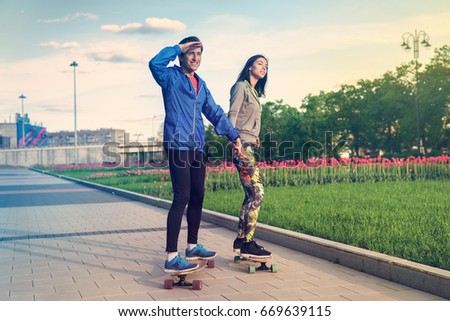A girl and a man are riding in the park on a longboard #669639115