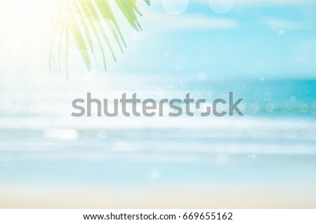 Blur beautiful nature green palm leaf on tropical beach with bokeh sun light wave abstract background.   #669655162