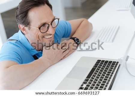 Adult man leaning on display and eying laptop #669693127
