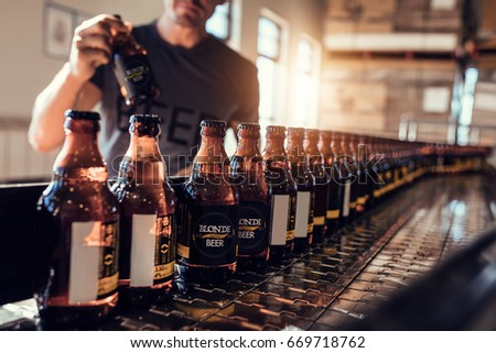 Conveyor with beer bottles moving in brewery factory. Young man supervising the beer bottling process and checking the quality at the manufacturing plant. Royalty-Free Stock Photo #669718762