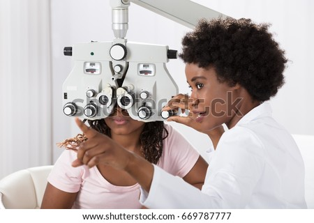 Female African Optometrist Doing Sight Testing For Patient In Hospital #669787777