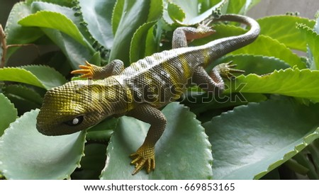 Toy Iguana Lizard like Reptile in Plastic Material for Outdoor, Halloween, Party, Decoration, on Green Leaves #669853165