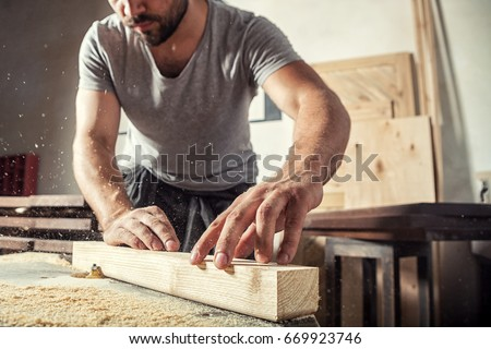 A young male carpenter builder in a gray T-shirt and working overall equals a wooden bar with a milling machine in the workshop, in the background wooden boards #669923746