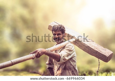 Happy Indian farmer standing with wooden plough in rice field #669966034