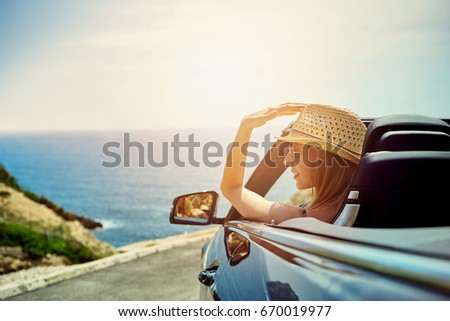 Back view of woman sitting in cabriolet putting hand on door looking away on background of sea.  #670019977