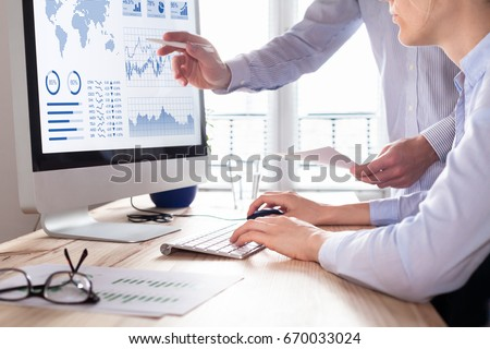 Two people analyzing stock market investment strategy with key performance indicator on financial dashboard and business intelligence on computer #670033024