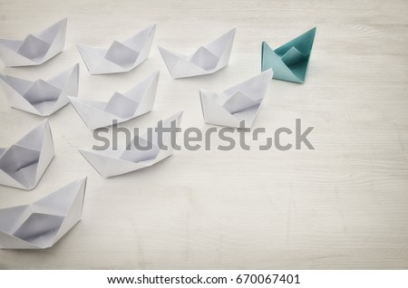 leadership concept, yellow paper boat leading followers over white wooden background. top view. Retro filtered #670067401