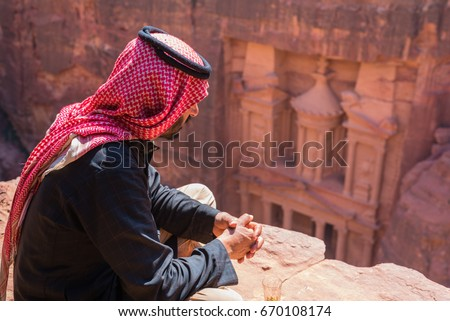 PETRA, JORDAN - 29 MARCH 2017: A bedouin looks at the treasury from an elevated point of view. #670108174